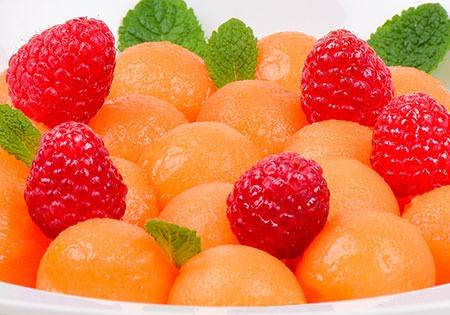 Photo boules de melon, framboises et feuilles de menthe